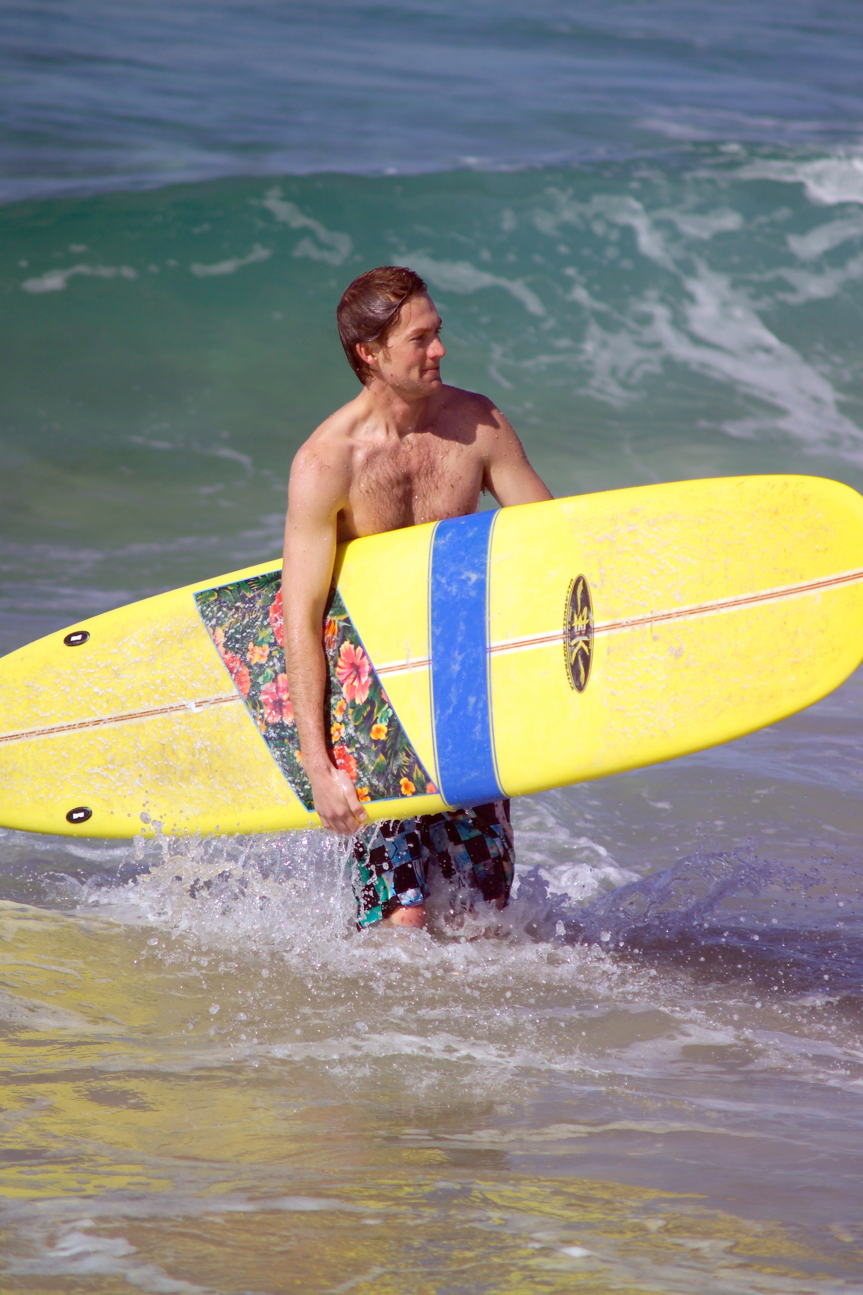 surfer with longboard coming out of surf